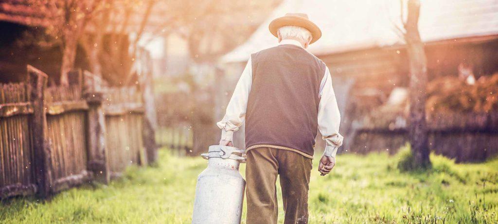 Man met een hoed aan de buitenkant van zijn woning