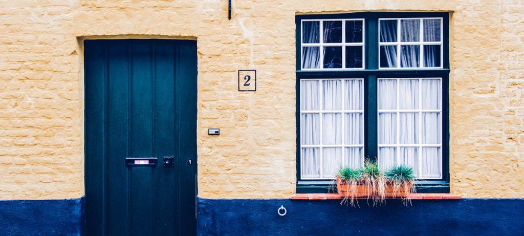 Devanture de maison jaune avec porte bleue