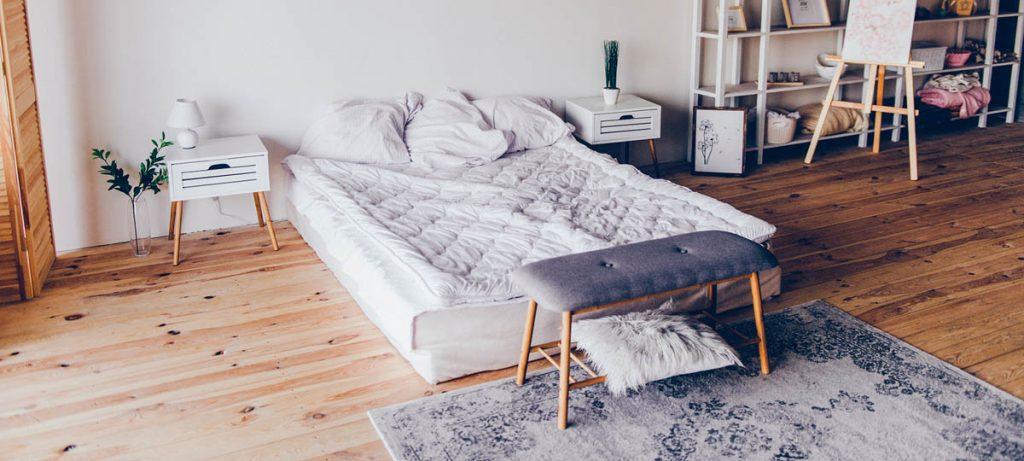 Chambre chaleureuse avec petit mobilier et plancher en bois