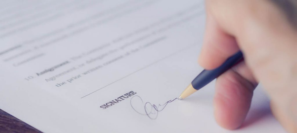 Person signing documents, closing the sale with a watertight compromise.