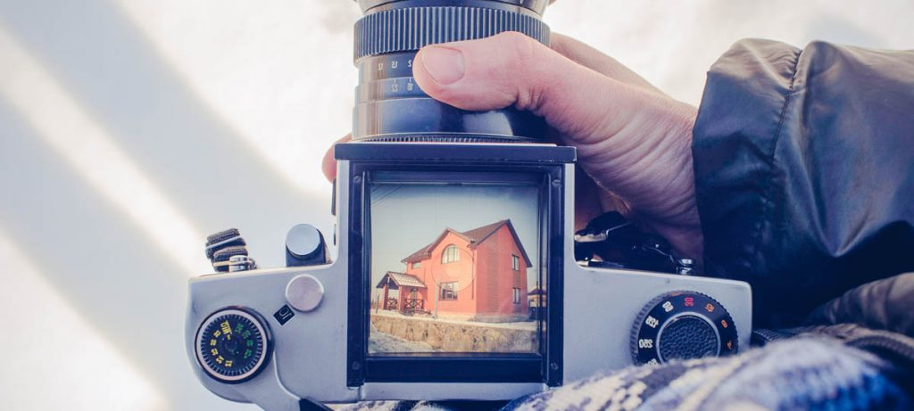 Person holding a camera with picture of house showing, renting or selling what is your best option.