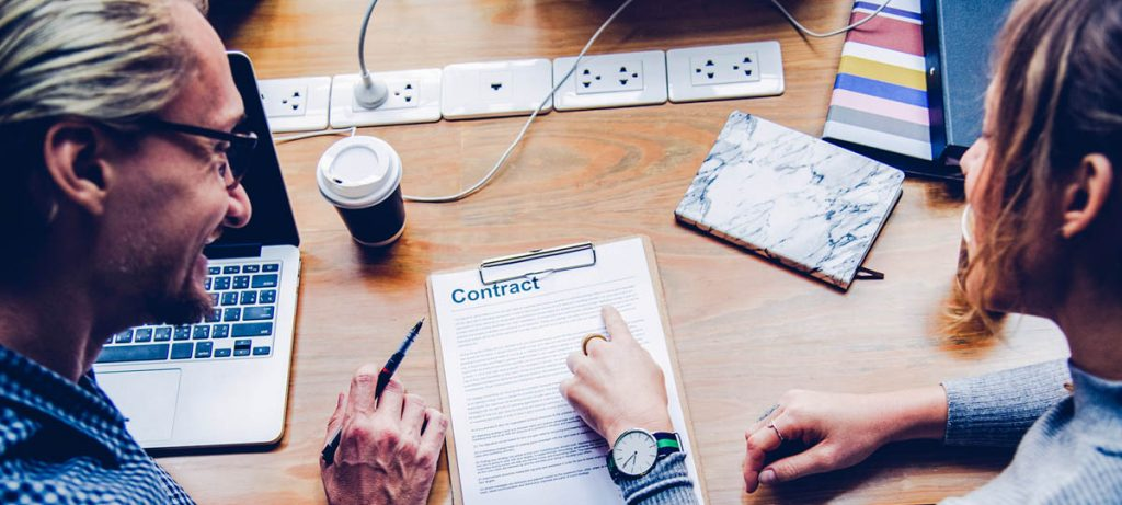 2 people looking over a contract together, ending your rental agreement early in a correct way.
