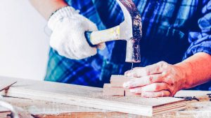 Person hammering a nail into several planks of wood, increasing the value of your home.