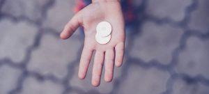 Twee munten in een hand om te betalen met een donkere achtergrond