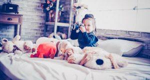 Meisje dat foto's maakt omringd door knuffels
