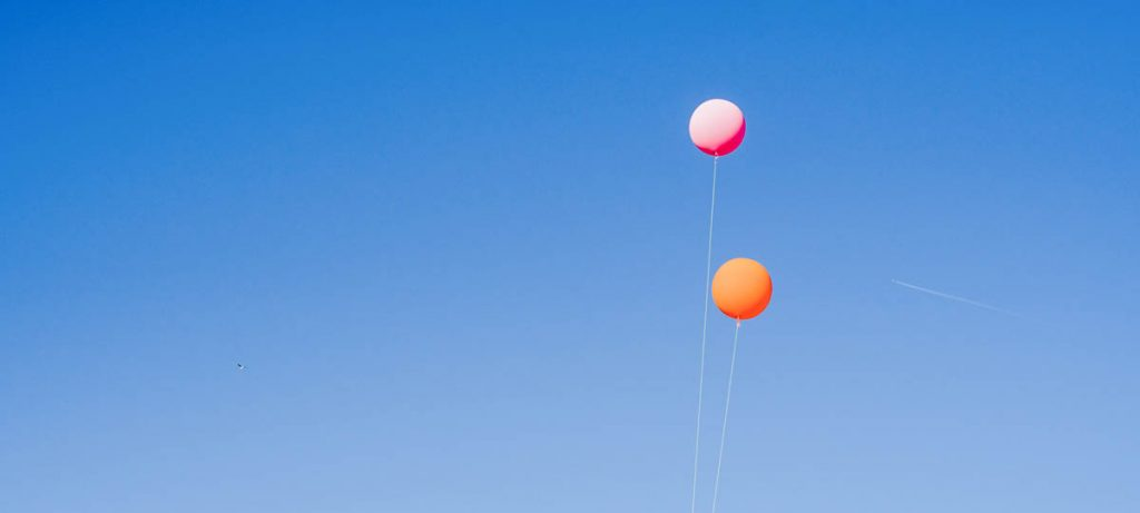 2 colourful balloons floating in the blue sky, finding the right insurance for your new home.