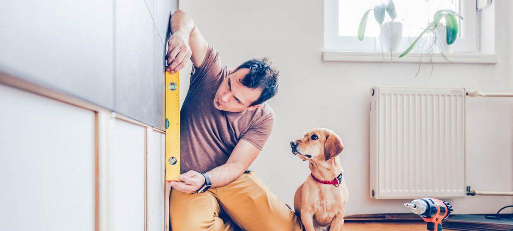 Homme dans son logement en train de prendre des mesures avec son chien