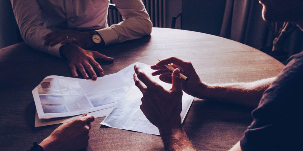 People sitting around a tabel discussing a property, making an offer on a property here is what you should know.