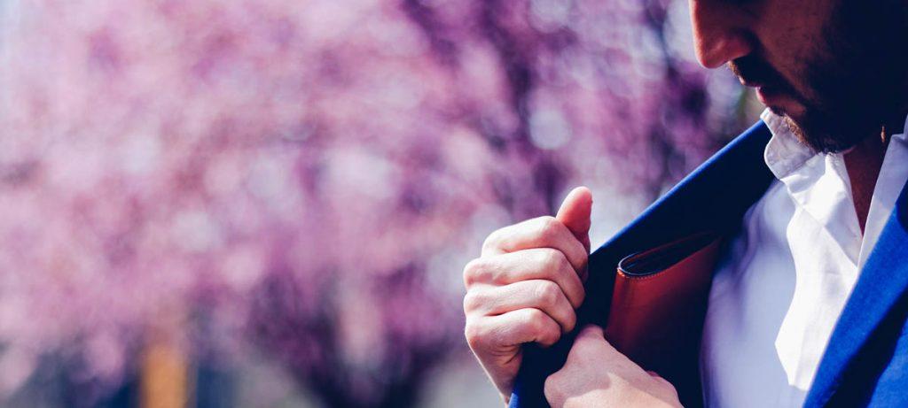 Man in profiel in pak met roze achtergrond