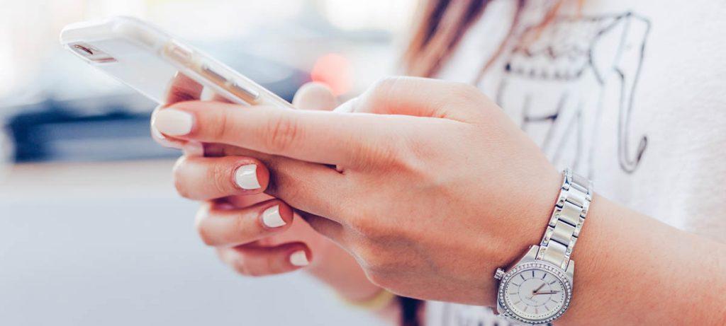 Vrouw met nagellak en horloge met een telefoon in de hand