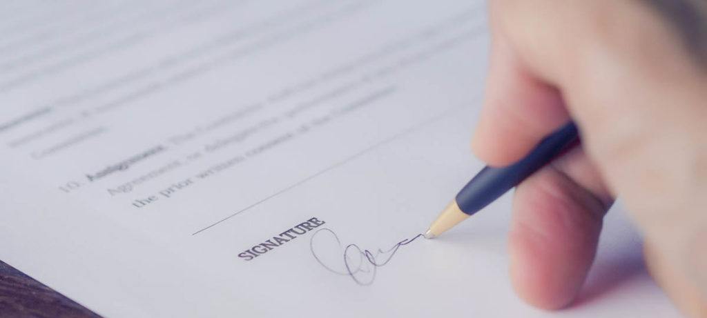 Personne en train de signer un document immobilier
