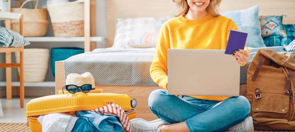 Femme avec un pull jaune qui tient un passport en travaillant sur son ordinateur