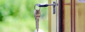 key unlocking wooden door, real estate market is booming