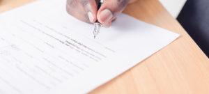 Persoon die een juridisch document met een pen ondertekent