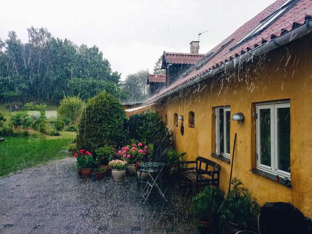 Huis met een grote tuin in de regen