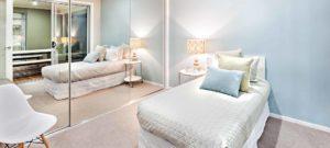 Interieur van een slaapkamer met een klein bed en een grote spiegel