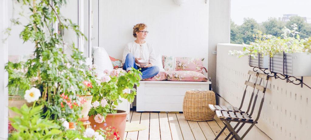 Femme assise sur une terrasse luxuriante et lumineuse