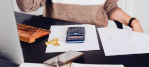 Man met een rekenmachine en bladeren om zijn lening te herzien.