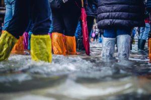 des personnes munies de bottes de pluie en cas de dégâts des eaux