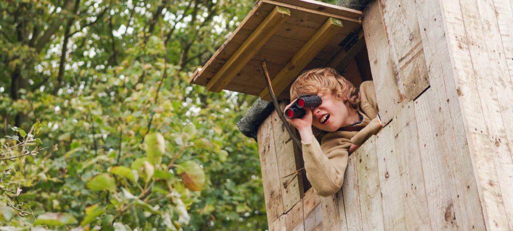 garçon dans une cabane dans son jardin